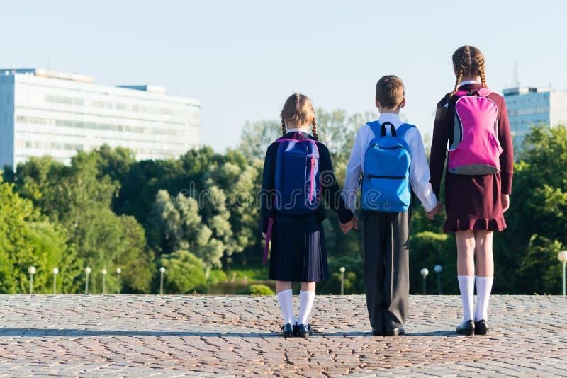 Tre allievi in uniforme scolastico stanno sulla via con gli zainhi, retrovisione immagini stock