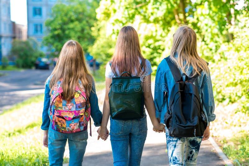 Tre amiche della scolara della ragazza Si tengono mani del ` s Estate in città Vista posteriore Camminano giù la via a fotografia stock libera da diritti