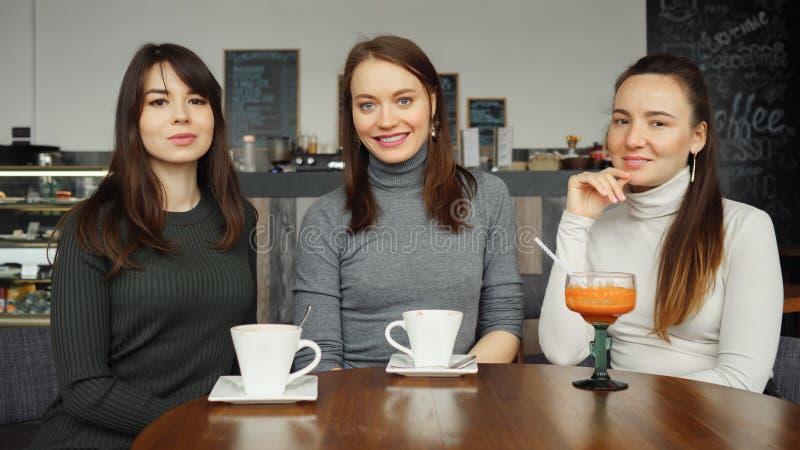 Tre amiche delle donne con le bevande in un caffè stanno parlando fotografie stock