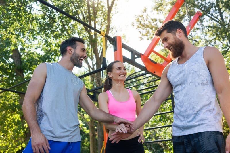Tre amici allegri che un le mani come gesto della motivazione immagine stock