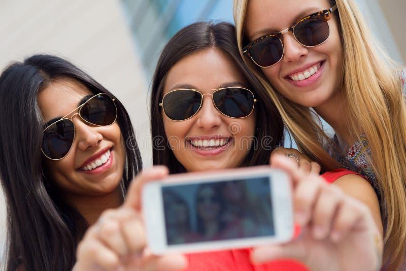Tre amici che prendono le foto con uno smartphone fotografia stock libera da diritti