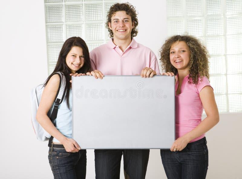 Tre amici con la tabella in bianco fotografie stock