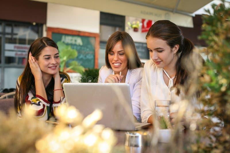 Tre amici delle giovani donne si divertono sulla pausa caffè fotografia stock libera da diritti
