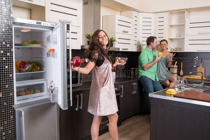 Tre amici divertendosi nella cucina fotografia stock