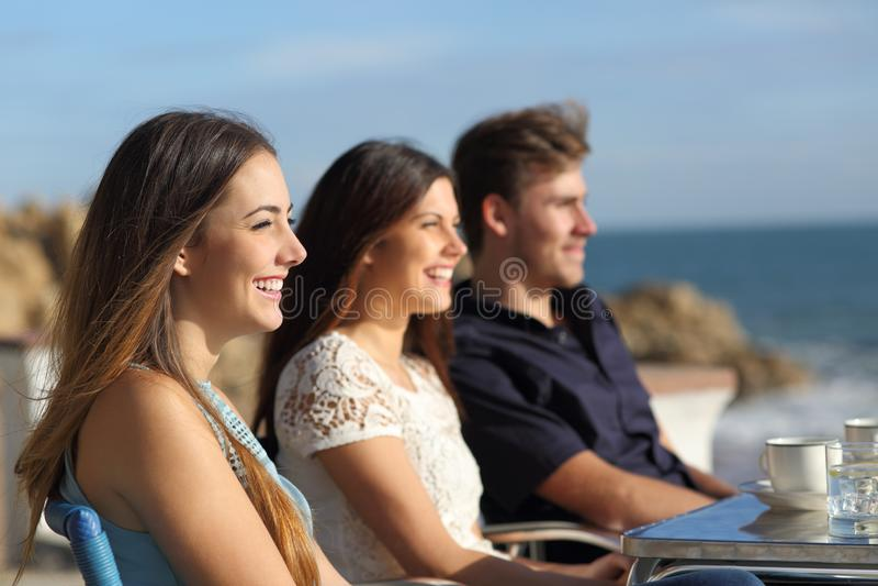 Tre amici felici che guardano la spiaggia in una caffetteria fotografia stock libera da diritti