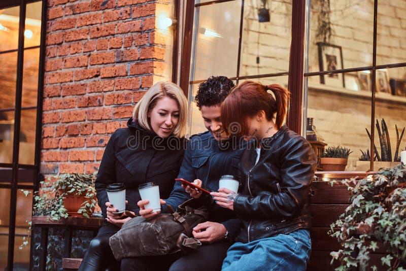 Tre amici felici che hanno una rottura con caffè che si siede vicino ad un caffè fuori immagine stock libera da diritti