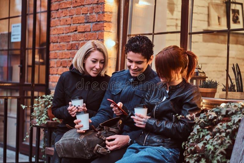 Tre amici felici che hanno una rottura con caffè che si siede vicino ad un caffè fuori immagine stock