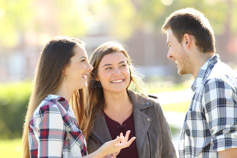 Tre amici felici che parlano nella via fotografie stock
