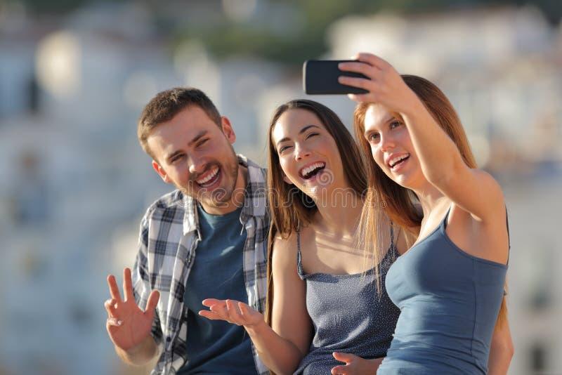 Tre amici felici che prendono i selfies nelle periferie di una città immagini stock