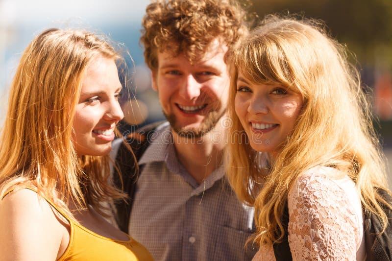 Tre amici felici dei giovani all'aperto fotografie stock