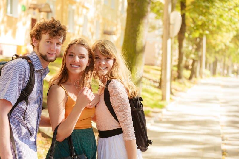 Tre amici felici dei giovani all'aperto fotografia stock