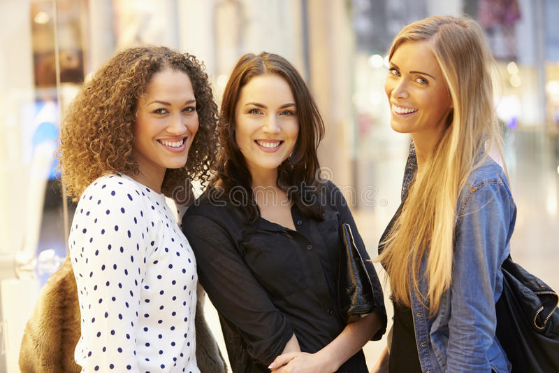 Tre amici femminili che comperano insieme nel centro commerciale fotografia stock