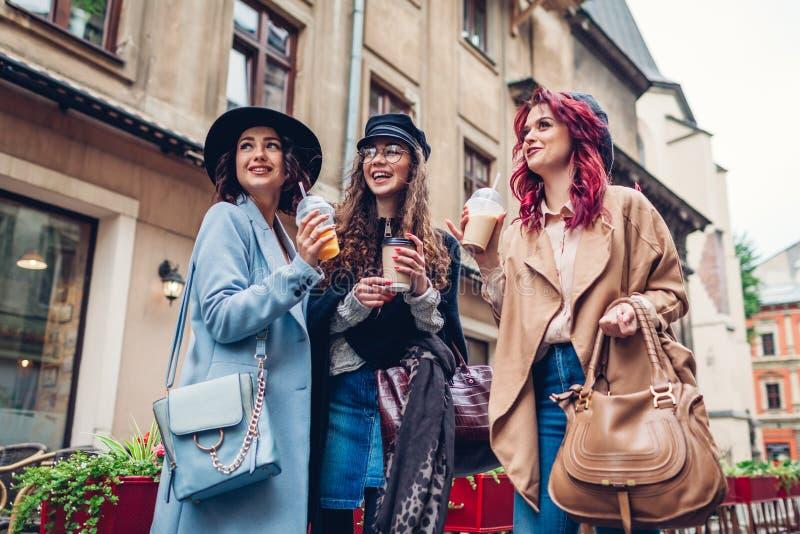 Tre amici femminili che hanno bevande all'aperto Donne tazze tintinnanti del caff?, del succo d'arancia e di t? fotografia stock