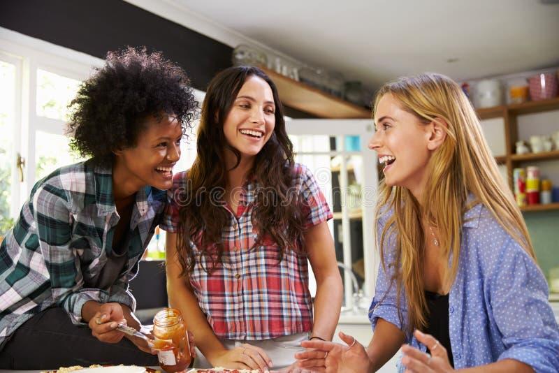 Tre amici femminili che producono insieme pizza in cucina immagini stock