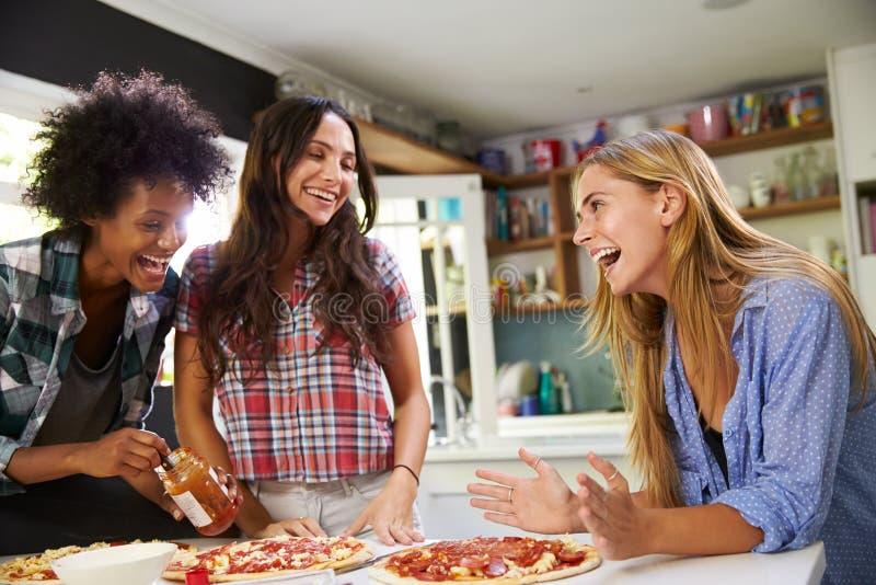 Tre amici femminili che producono insieme pizza in cucina fotografia stock