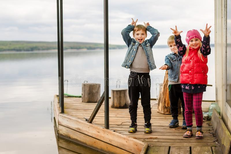 Tre amici giocano la pesca sul pilastro di legno vicino allo stagno Due ragazzi del bambino ed una ragazza alla sponda del fiume  immagine stock libera da diritti
