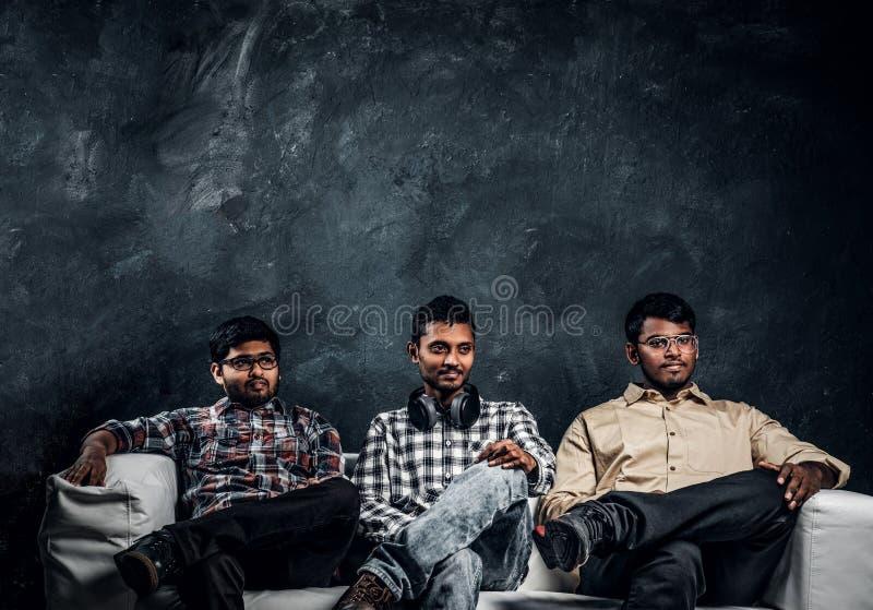 Tre amici indiani dello studente che indossano l'abbigliamento casual che si siede su un sofà contro la parete scura immagine stock libera da diritti