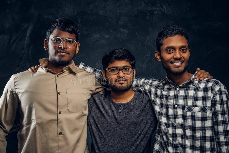 Tre amici indiani dello studente stanno in un abbraccio e esaminano la macchina fotografica in studio immagini stock libere da diritti