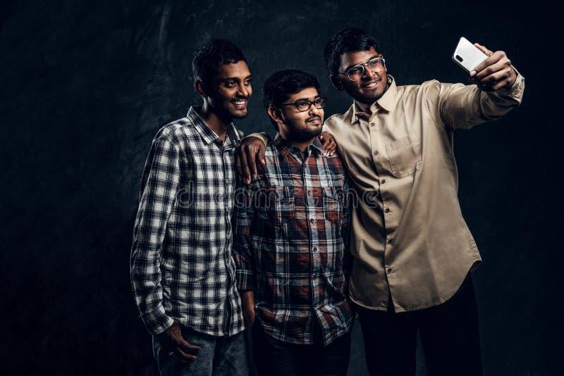 Tre amici indiani felici in abbigliamento casual stanno in un abbraccio e selfie di presa sullo smartphone fotografia stock libera da diritti