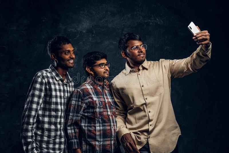 Tre amici indiani felici in abbigliamento casual stanno in un abbraccio e selfie di presa sullo smartphone fotografie stock