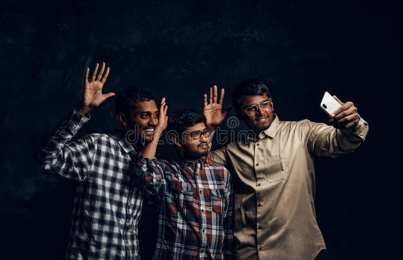 Tre amici indiani felici in abbigliamento casual stanno in un abbraccio e selfie di presa sullo smartphone immagini stock libere da diritti