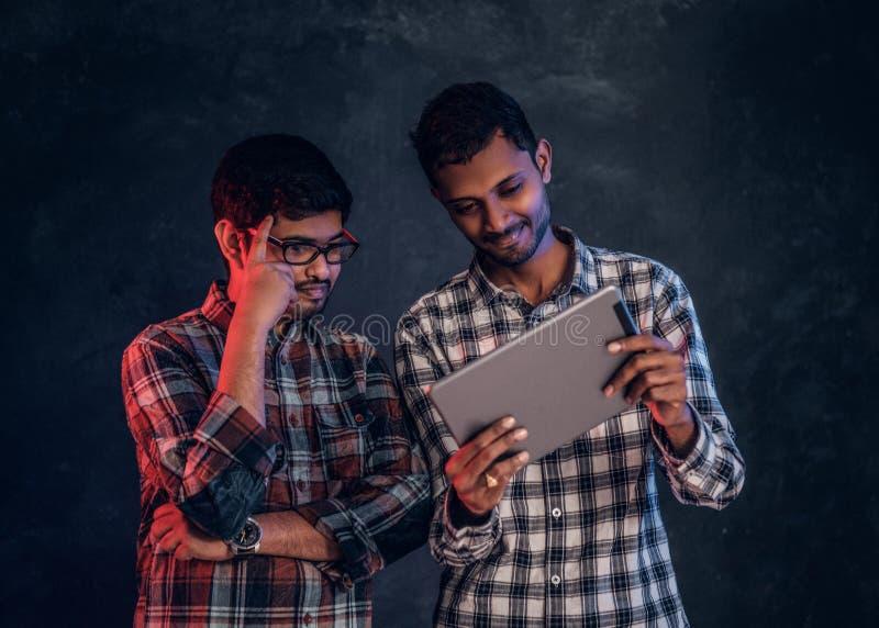 Tre amici indiani felici in abbigliamento casual stanno in un abbraccio e selfie di presa sullo smartphone fotografie stock libere da diritti