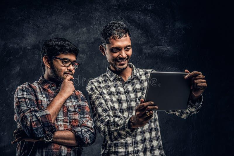 Tre amici indiani felici in abbigliamento casual stanno in un abbraccio e selfie di presa sullo smartphone immagine stock