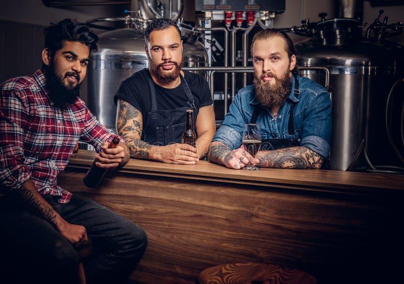 Tre amici interrazziali barbuti bevono la birra del mestiere in una fabbrica di birra fotografia stock