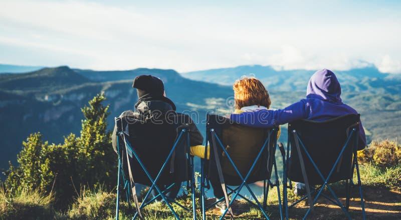 Tre amici si siedono nelle sedie di campeggio sopra una montagna, i viaggiatori godono della natura e l'abbraccio, turisti esamin immagini stock