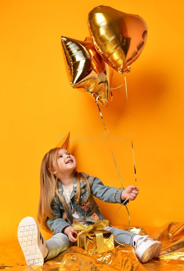 Tre anni della ragazza di bambino del bambino con i palloni dei presente dell'oro e compleanno ricoprono la celebrazione fotografia stock