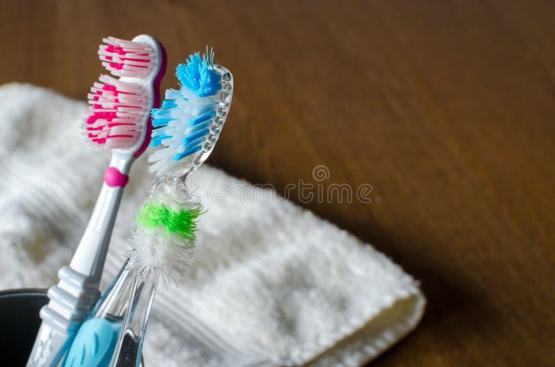 Tre använde plast- tandborstar med handduken på träbakgrund Kopiera utrymme för text fotografering för bildbyråer