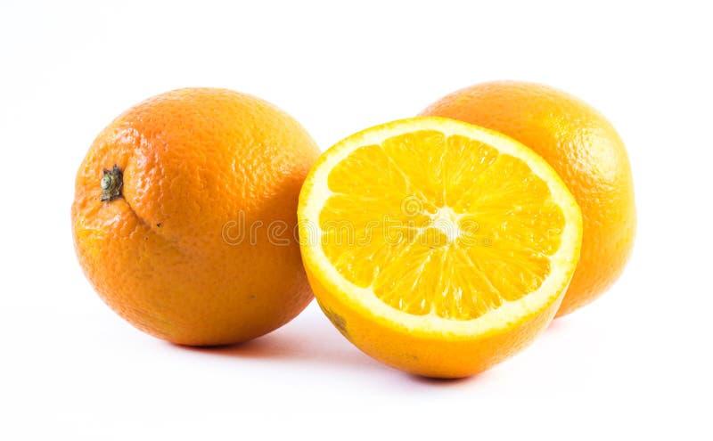 Tre arance piacevolmente colorate su un fondo bianco - la parte anteriore e la parte posteriore hanno tagliato a metà immagini stock