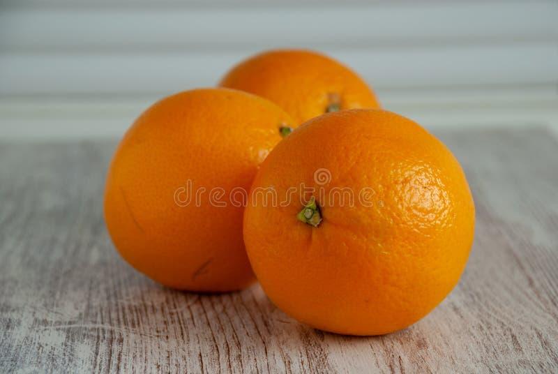 Tre arance su fondo di legno bianco fotografia stock libera da diritti