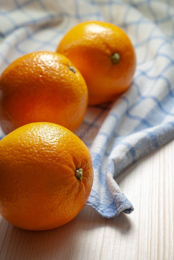 Tre arance su legno leggero immagini stock libere da diritti