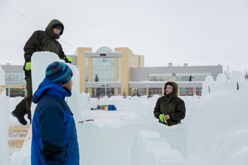 Tre arbetare som talar på konstruktionsplatsen arkivbild