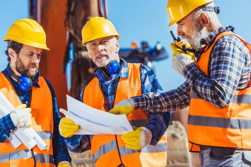 Tre arbetare som undersöker byggnadsplan och talar på bärbar radio arkivbild