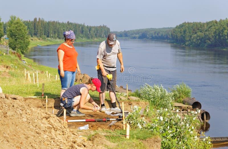 Tre archeologi stanno cercando i piccoli oggetti del metallo nel suolo sparso per mezzo di un metal detector immagine stock