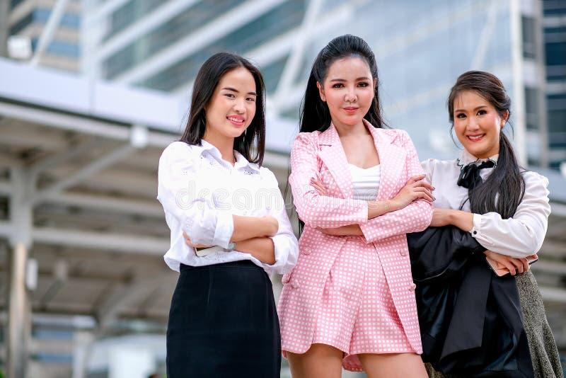Tre asiatiska affärsflickor agerar som säkert med deras arbete och ler för att uttrycka av lyckligt under dagtid utanför arkivfoto