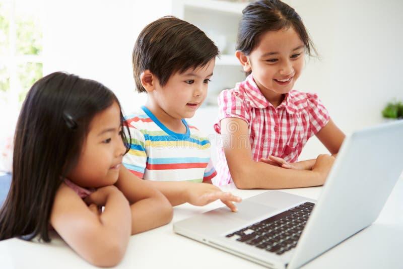 Tre asiatiska barn som hemma använder bärbara datorn royaltyfri fotografi