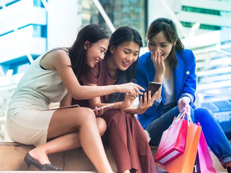 Tre asiatiska kvinnor för lycka intresserar något innehåll från s royaltyfri bild