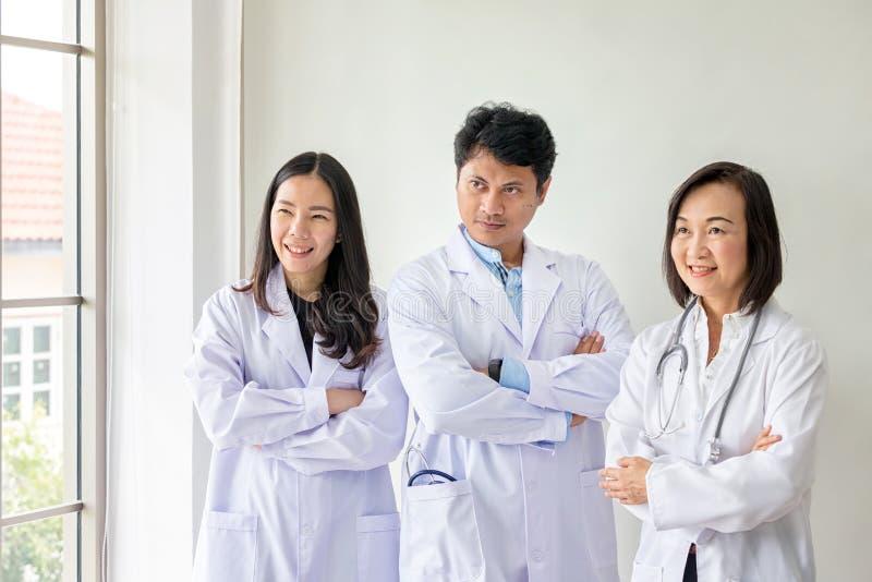 Tre asiatiska medicinska arbetare ler St?ende av den asiatiska doktorn Kemister som g?r i laboratoriumet unga forskare med provet fotografering för bildbyråer