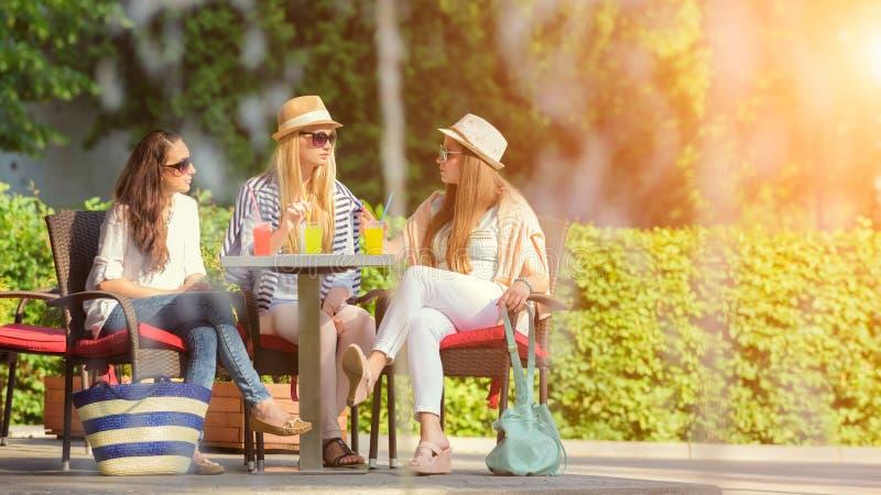 Tre attraktiva flickvänner som tycker om coctailar i ett utomhus- kafé arkivbilder