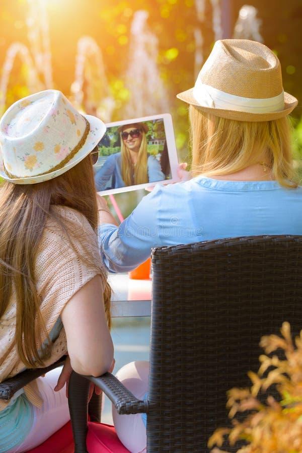 Tre attraktiva hipsterflickor som tar en selfie med den digitala minnestavlan fotografering för bildbyråer