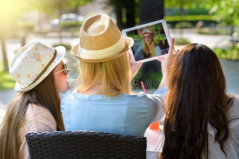 Tre attraktiva hipsterflickor som tar en selfie med den digitala minnestavlan royaltyfri fotografi