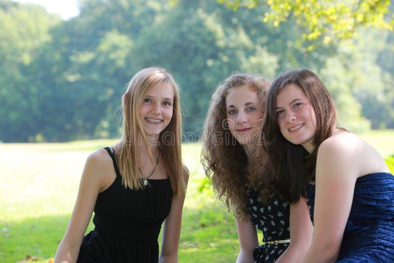 Tre attraktiva lyckliga unga tonårs- flickor som tillsammans sitter arkivfoto