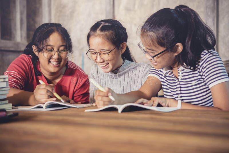 Tre av den gladlynta asiatiska tonåringen som är orubblig för skolaläxamummel royaltyfri bild