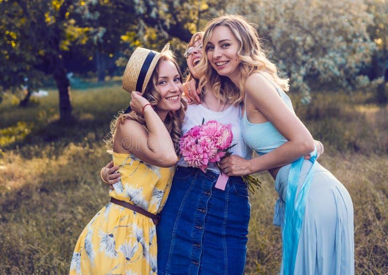 Tre av flickavänner som är utomhus- i parkera eller skogen arkivbilder