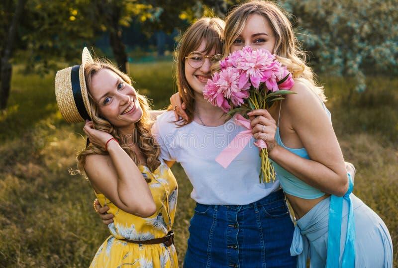 Tre av flickavänner som är utomhus- i parkera eller skogen royaltyfri bild