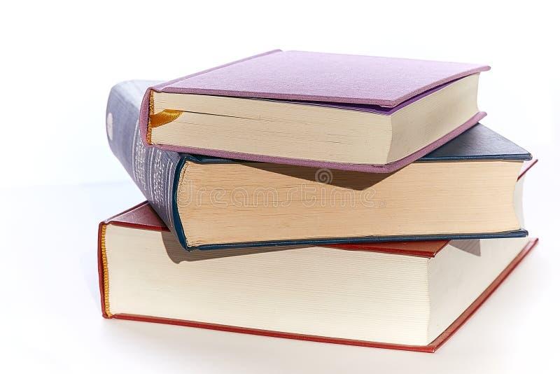 Tre böcker slut-UPS av olika färger ligger överst av de Bakgrundsvit royaltyfria bilder