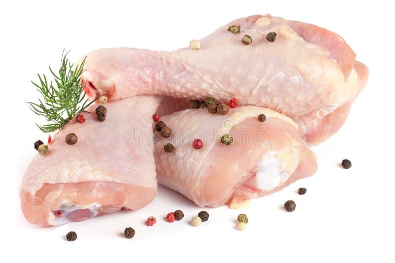 Tre bacchette di pollo crude con un ramoscello di aneto e dei granelli di pepe isolati su fondo bianco immagine stock libera da diritti